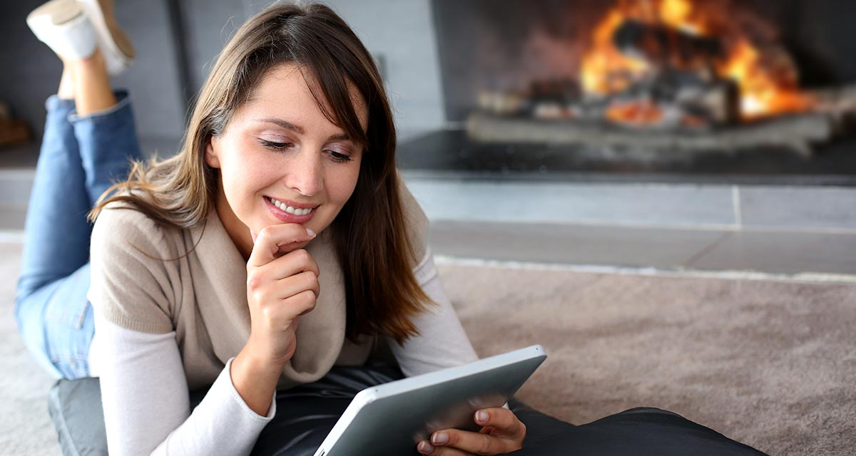 Woman lying on floor looking at tablet in front of fireplace